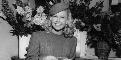 1948  american actor and singer doris day smiling as she sits in front of bouquets of flowers in her dressing room on the set of director michael curtizs film, romance on the high seas she wears a tailored suit, a wool hat, and has long hair  photo by hulton archivegetty images
