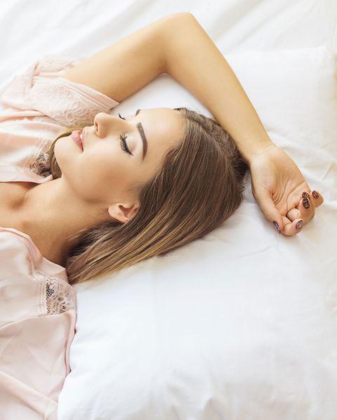 una mujer joven duerme en una cama con sábanas blancas
