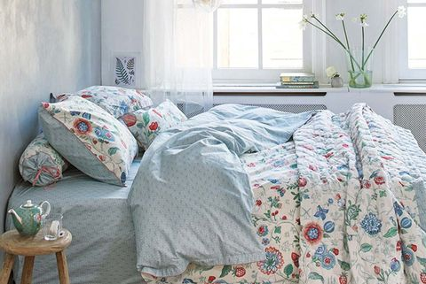 Dormitorio azul con funda nórdica de flores