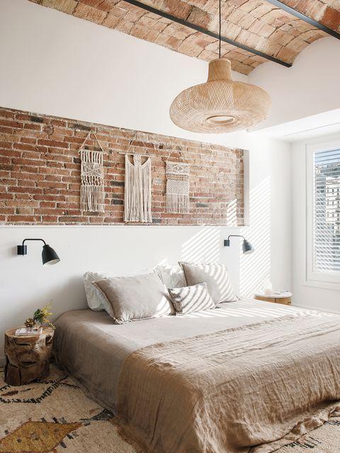 una casa decorada con esencia boho  dormitorio con hornacina de ladrillo