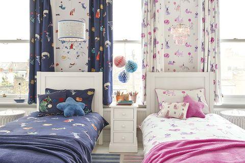 dormitorio infantil con dos camas y papel pintado a juego con las cortinas estampadas