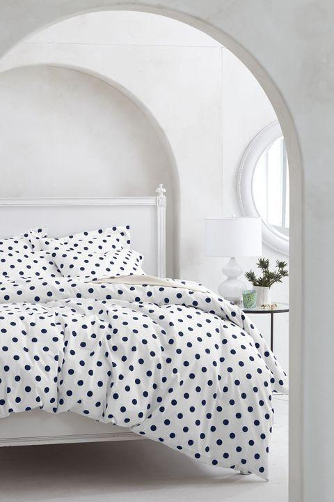 Dormitorio en blanco con ropa de cama de lunares