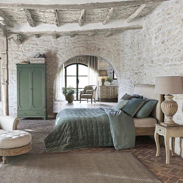 dormitorio con paredes de piedra y vigas con ropa de cama verde