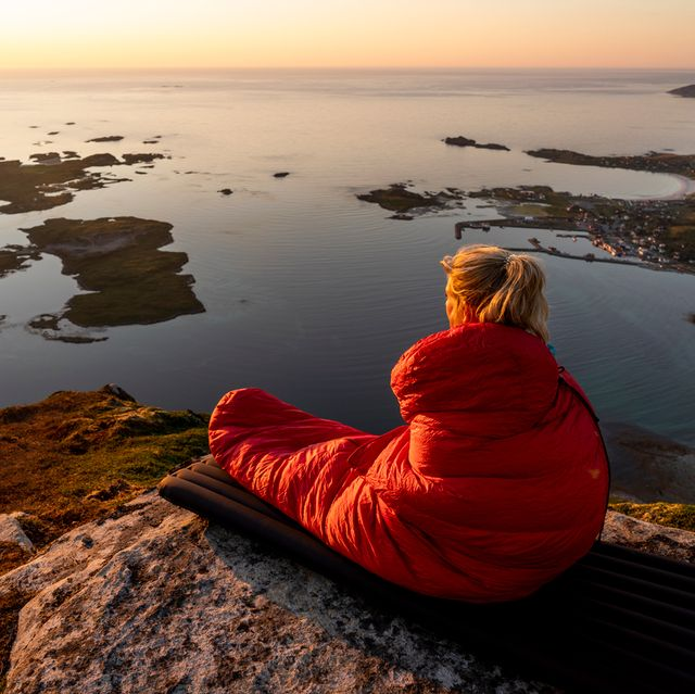 woman in sleeping bag looking over cliff at sunrise