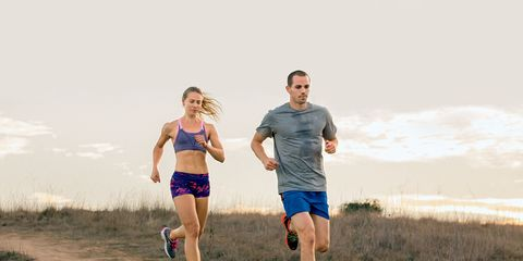 Couple running downhill on a dirt trail