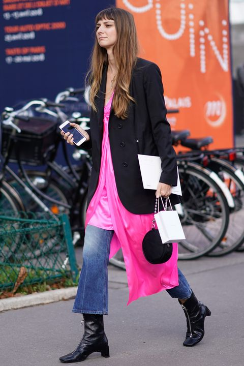 A street styler wearing a dress over jeans