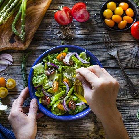 Dressing fresh organic vegetables salad with olive oil