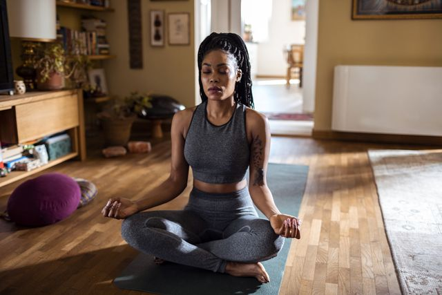 close up of a young woman meditating at home