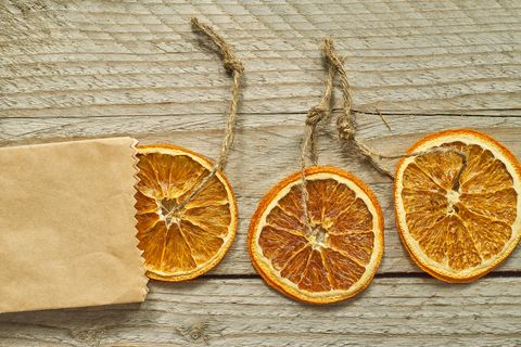 christmas decor dried orange slice in craft paper package on wooden background, top view, minimal flat lay