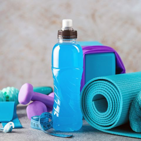 Drink isotonic bottle and fitness equipment on a grey background. Sport, fitness or yoga concept