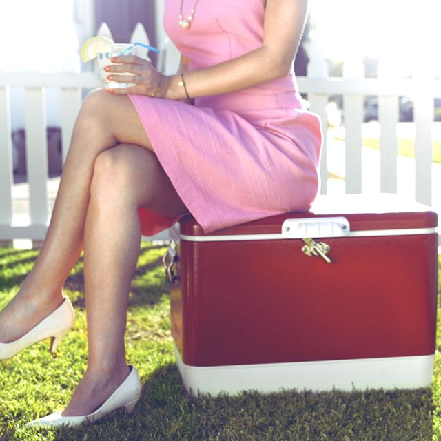 woman in a pink dress sitting on a red cooler