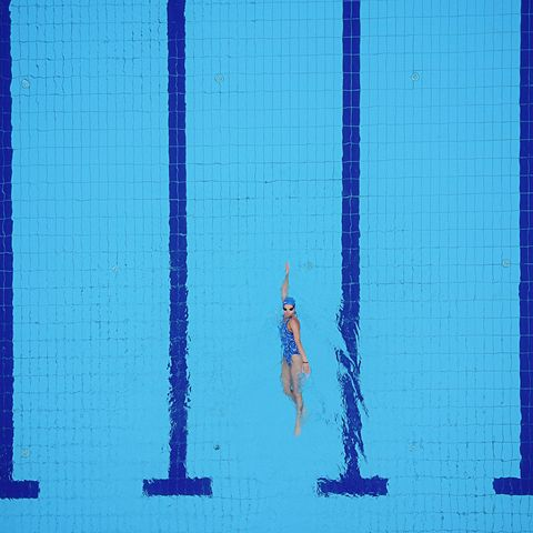 Drone point of view on swimming pool and female backstroke swimmer
