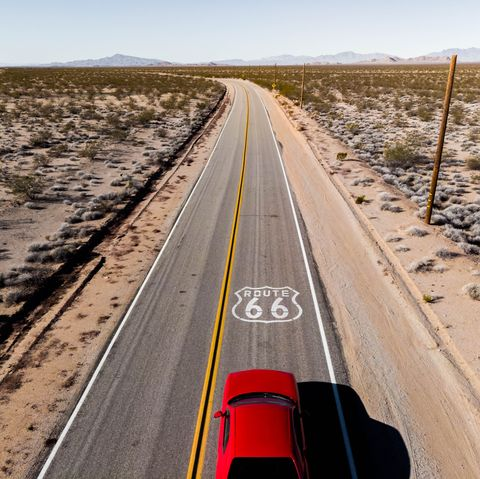 Drone view of American car driving in a straight road at the California desert.