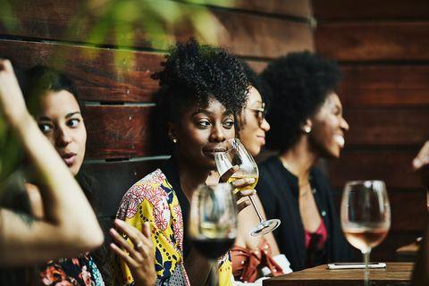 Vrouw drinkt een glas wijn met haar vrienden