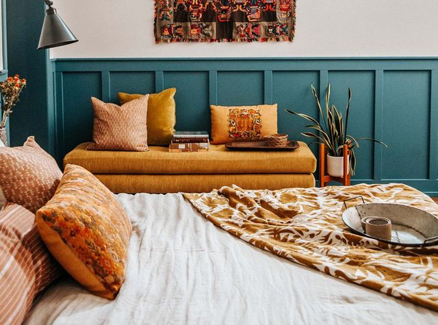 bedroom, bed, yellow cushioned bench, tapestry on wall