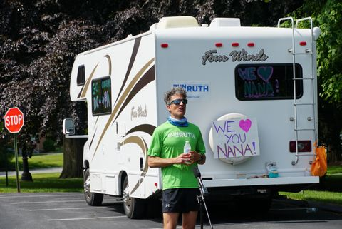 "corey cappelloni pauses during a run by the rv that his girlfriend was driving a sign off the back of the rv reads, ""we love you nana"""