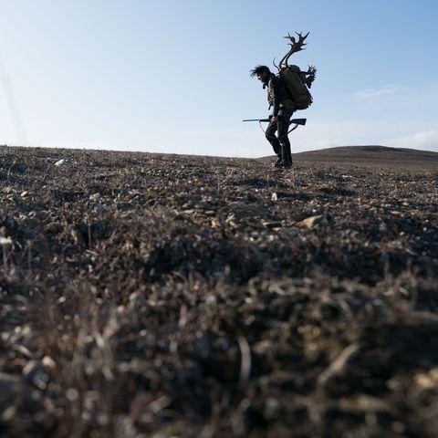 man carrying a lot of weight over barren landscape