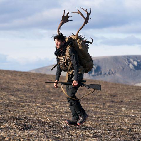 man carrying caribou through desolate landscape