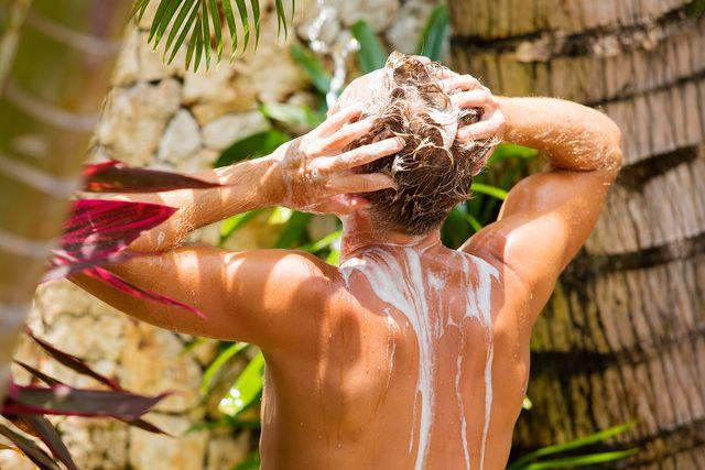 man washing hair outdoors in tropical garden