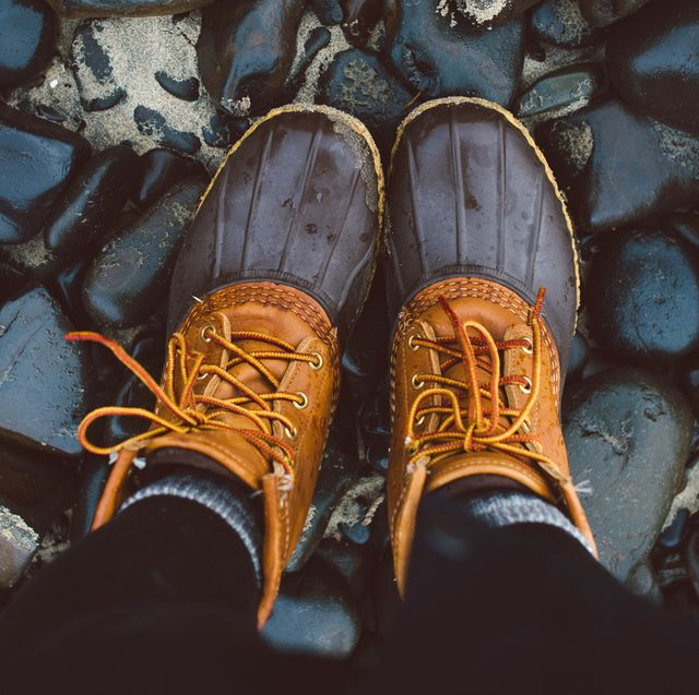 person wearing duck boots on top of wet rocks