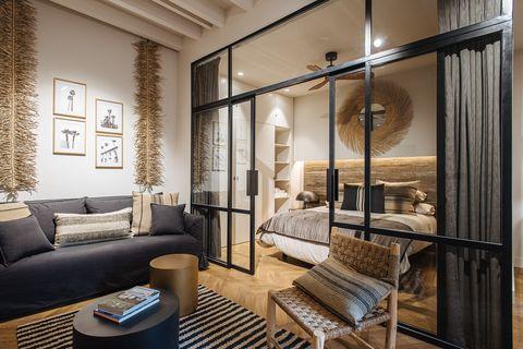 salón decorado en madera y fibras naturales junto a un dormitorio con cerramiento de vidrio con perfilería metálica