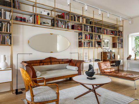 salón con librería de latón y muebles de anticuario