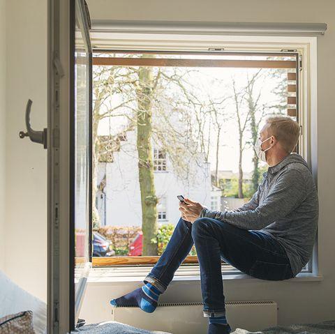 hombre con mascarilla sentado en el borde de la ventana