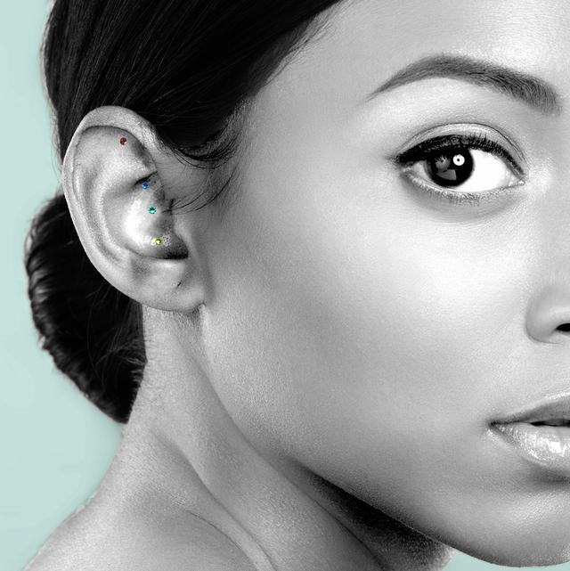 a woman wearing jewel toned ear seeds