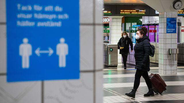 varias personas caminan con mascarillas en el metro de estocolmo