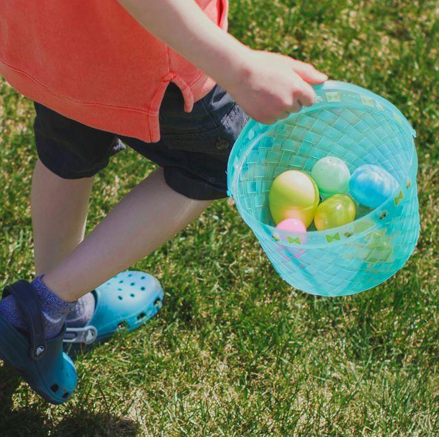 kid holding blue easter basket wearing crocs