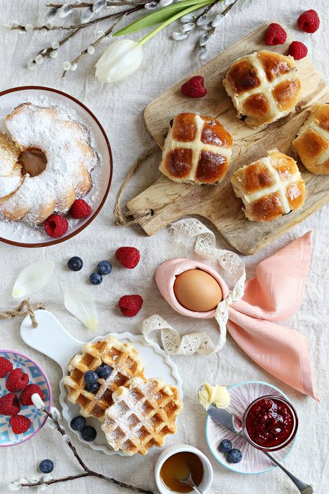 easter festive dessert table with hot cross buns, cakes, waffles and pancakes overhead view
