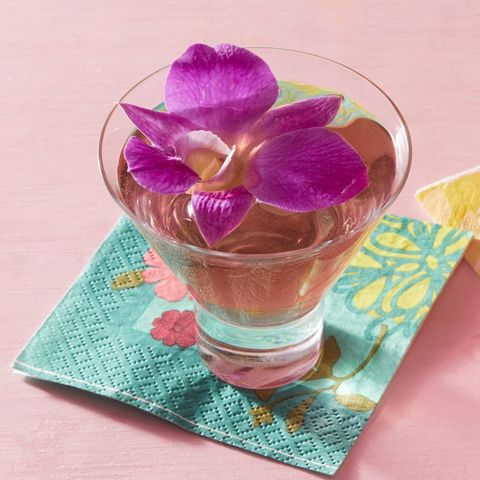 martini in stemless glass with purple orchid flower on top and blue floral napkin