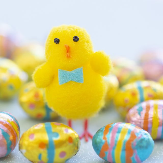a pom pom and felt easter chick surrounded by chocolate easter eggs