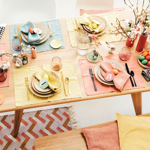 table decorated for easter with pastel placemats dishes eggs and vases of flowers