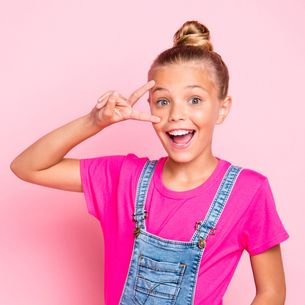 cute cheerful girl showing a peace sign in denim overalls and a pink shirt