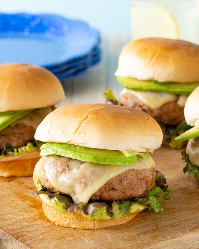 4 turkey burgers on wood board with lemonade