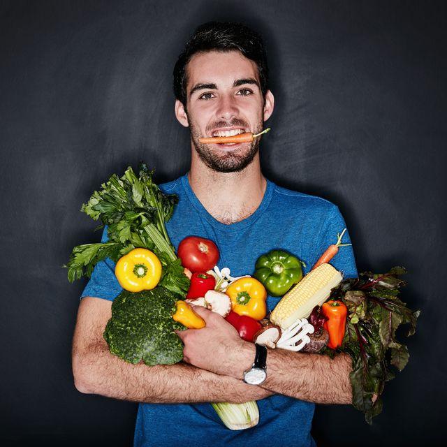 deportista sosteniendo frutas y verduras