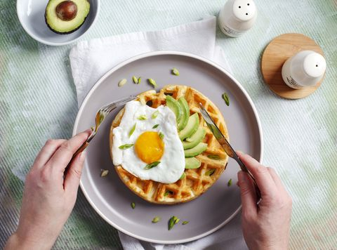 eating breakfast with savory waffles, fried eggs and avocado