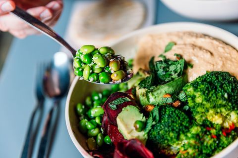 eating vegan bowl with edamame beans, broccoli, avocado, beetroot, hummus and nuts