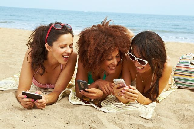 young women on beach with cell phones
