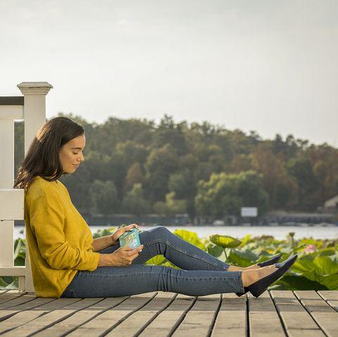 chica sentada en un porche de madera jugando con la nintendo switch a animal crossing new horizons
