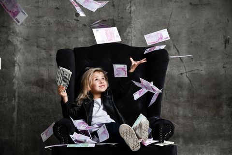 Kid girl in leather jacket is sitting in luxury armchair with her hand up under money rain catching dollars euro on gray