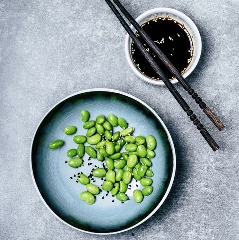 plate of edamame with chopsticks and bowl of soy sauce or coconut aminosEdamame