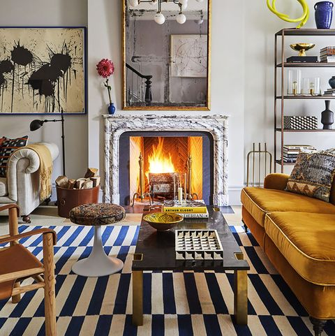 living room with striped rug, orange sofa and fireplace