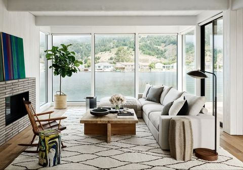 the living room of a marin county, california, home designed by nicole hollis features views of the water and the marin headlands in the distance a sectional sofa by flexform, a rocking chair by george nakashima, and a ceramic stool by artist reinaldo sanguino surround a cocktail table from galerie half the moroccan rug is by tony kitz