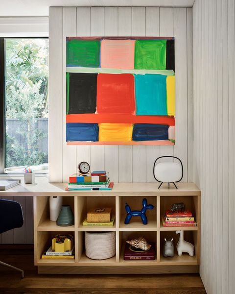 in one of the children's bedrooms, a balloon dog bookend by jeff koons sits in a cubby below a painting by stanley whitney