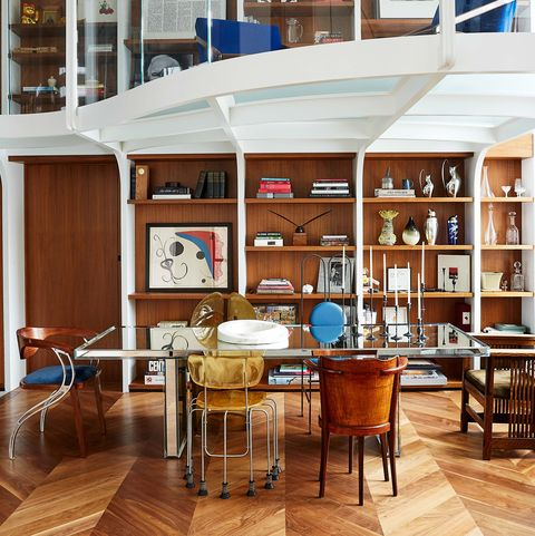 open plan  living-dining room with glass table and wooden shelving