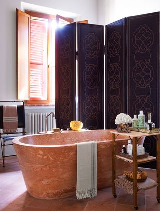 bathroom with large wooden tub