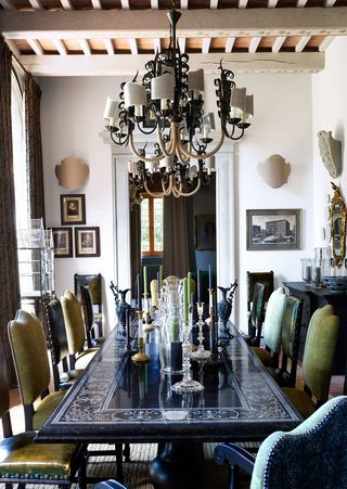 black dining table with leather chairs  and chandelier center
