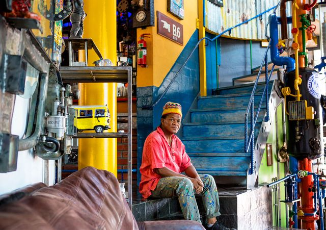 artist willie bester seated inside his home
